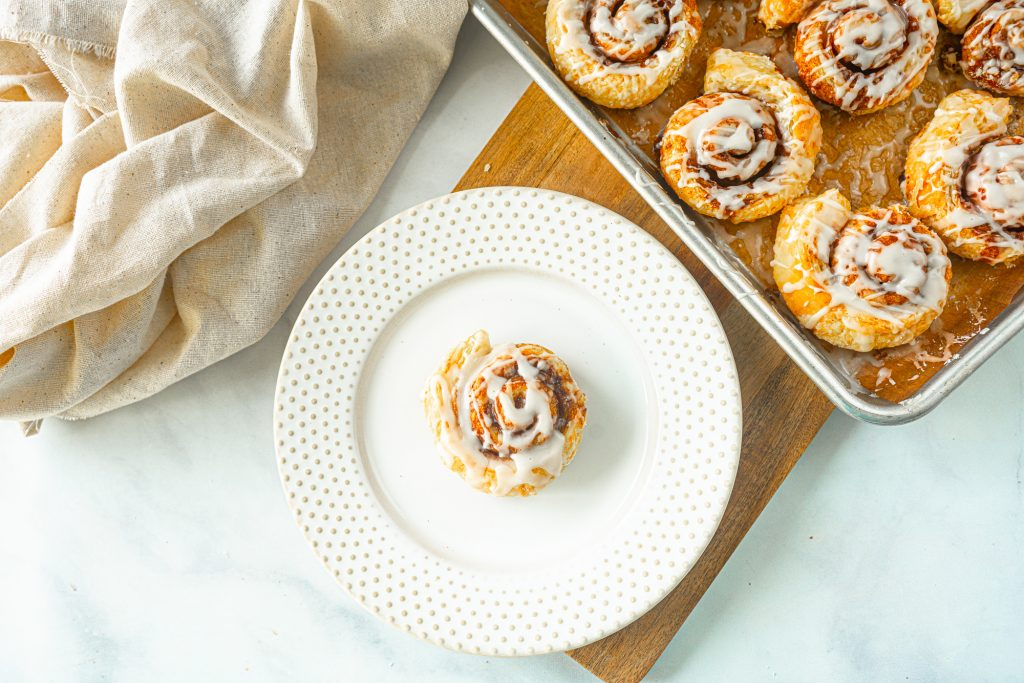 single vegan cinnamon roll on a plate with baking dish next to it
