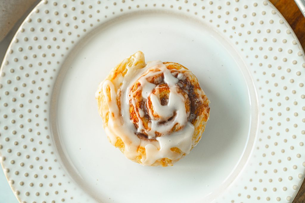 vegan cinnamon roll with glaze on plate