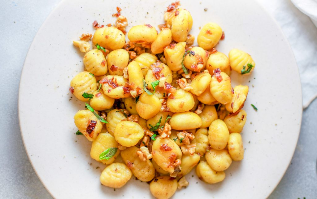 vegan gnocchi on a plate topped with onions and mushrooms