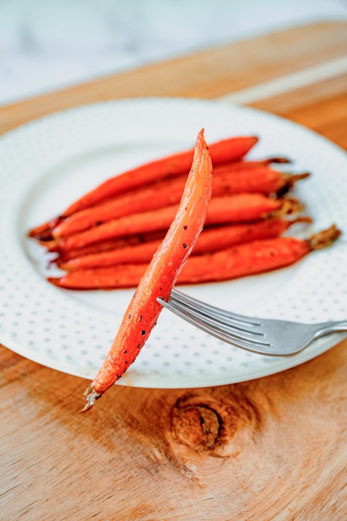 maple glazed carrot on the end of a fork with other carrots in the background