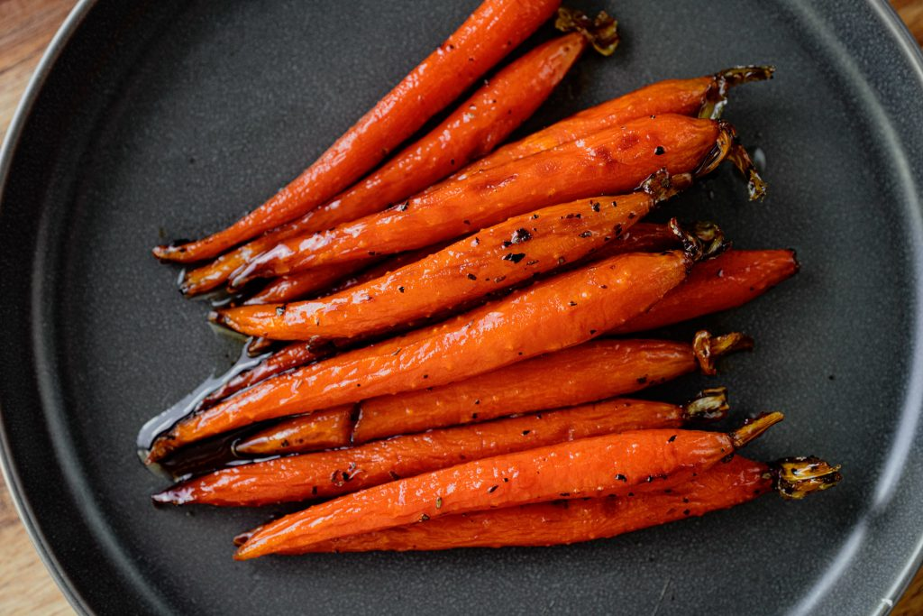 vegan maple glazed carrots on a black plate