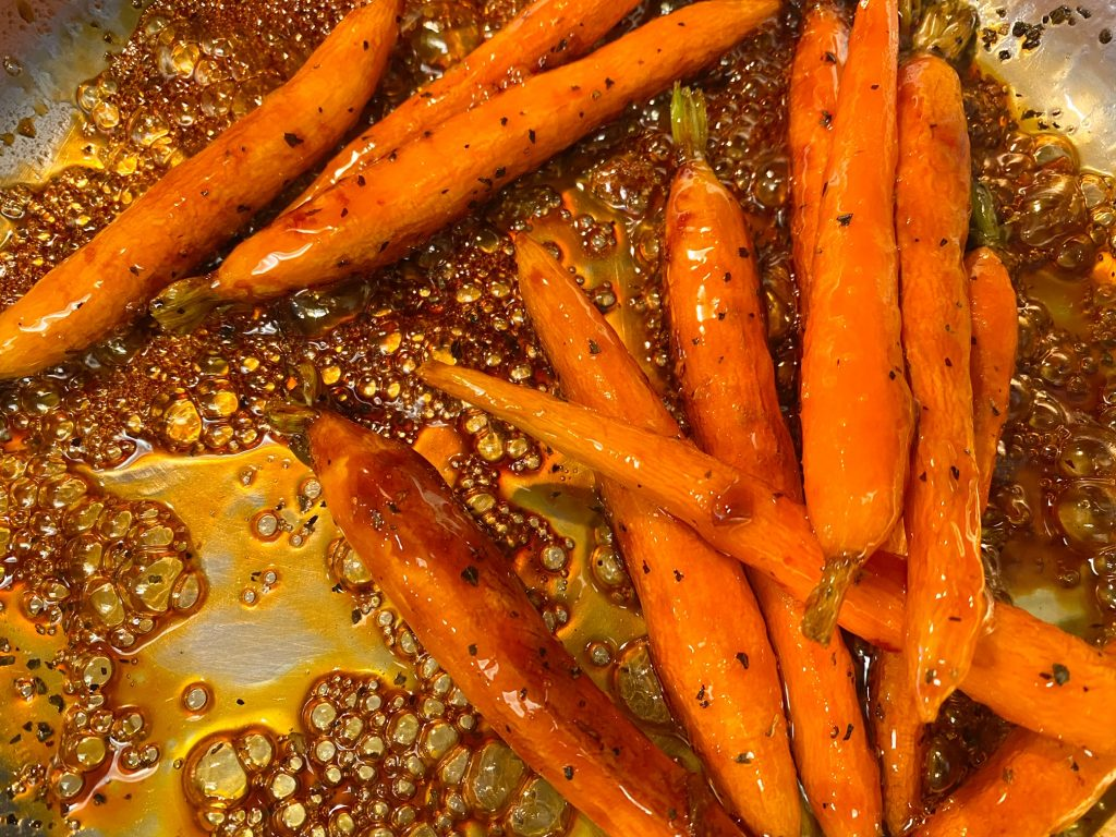 vegan and oil-free maple glazed carrots being cooked