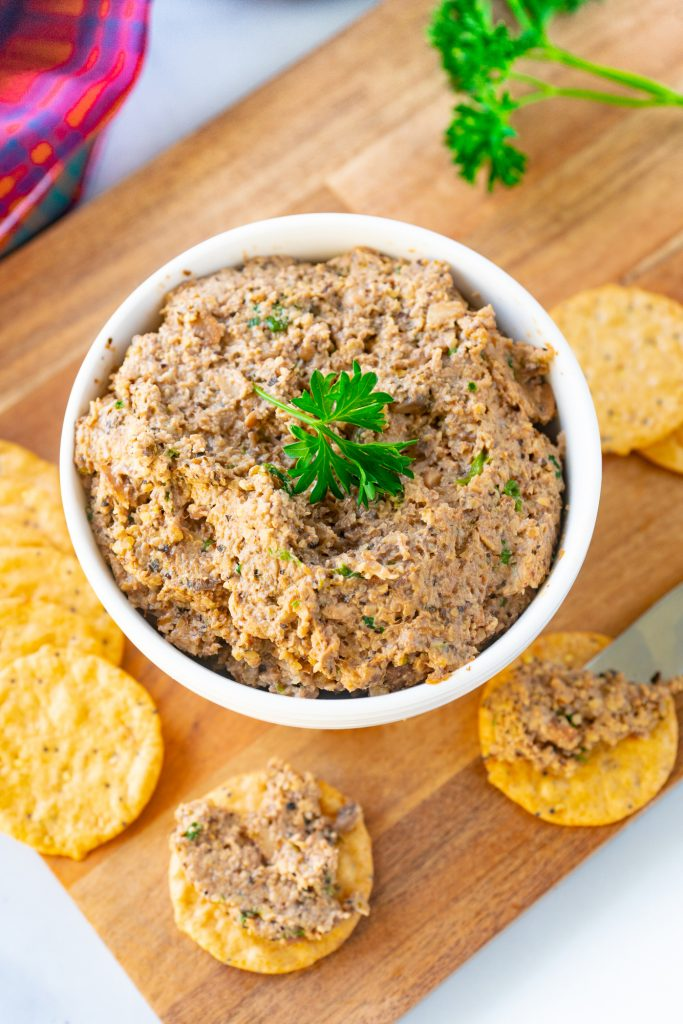 Photo of vegan pate being served in a white round bowl with crackers.