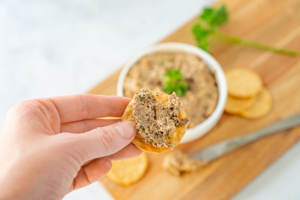 hand holding a cracker with vegan mushroom pate spread on it