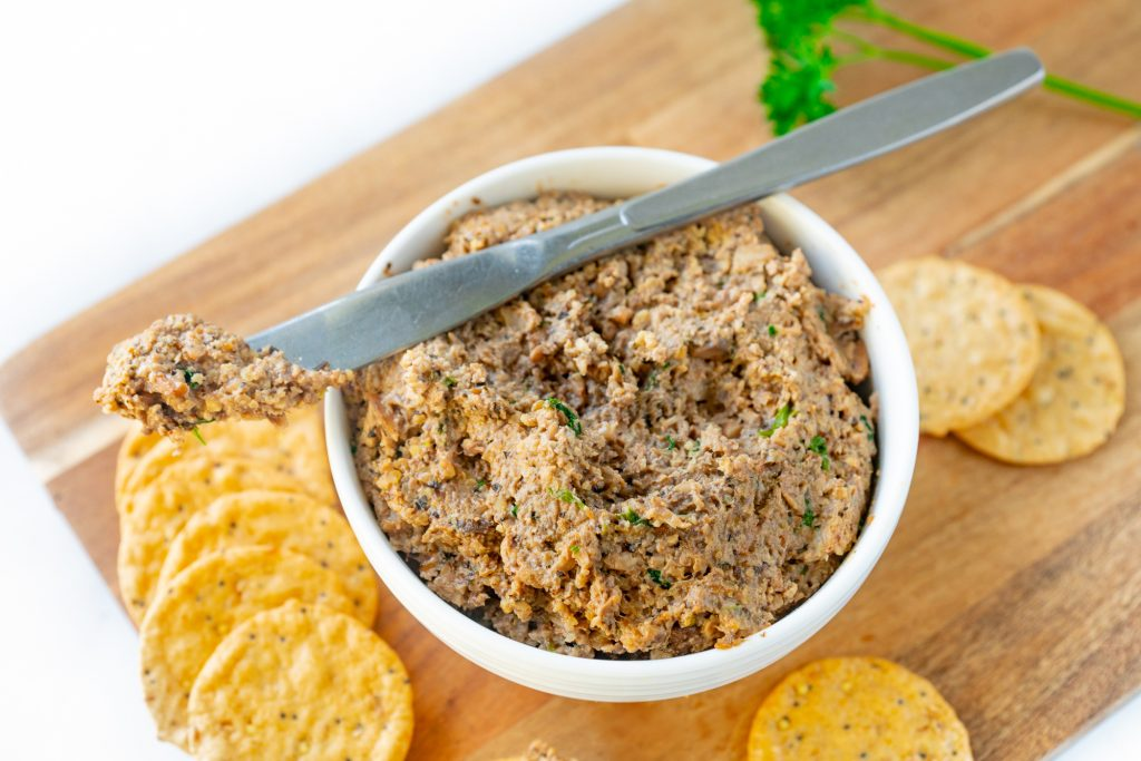 vegan mushroom pate in a bowl with a knife and crackers