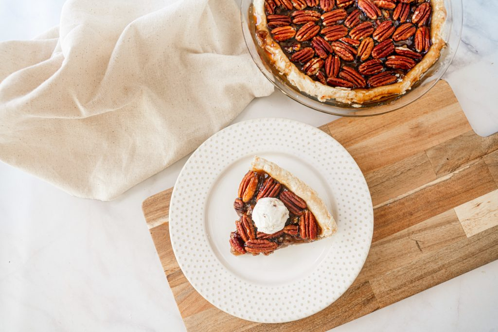 above photo of a slice of vegan pecan pie with pie in the background