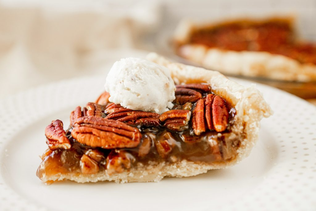 vegan pecan pie slice with vegan ice cream on top