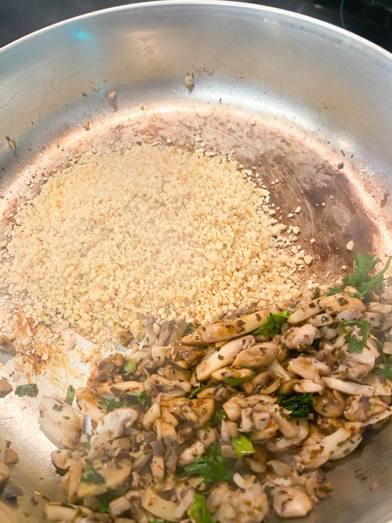 ground walnuts in a pan with saute mushrooms