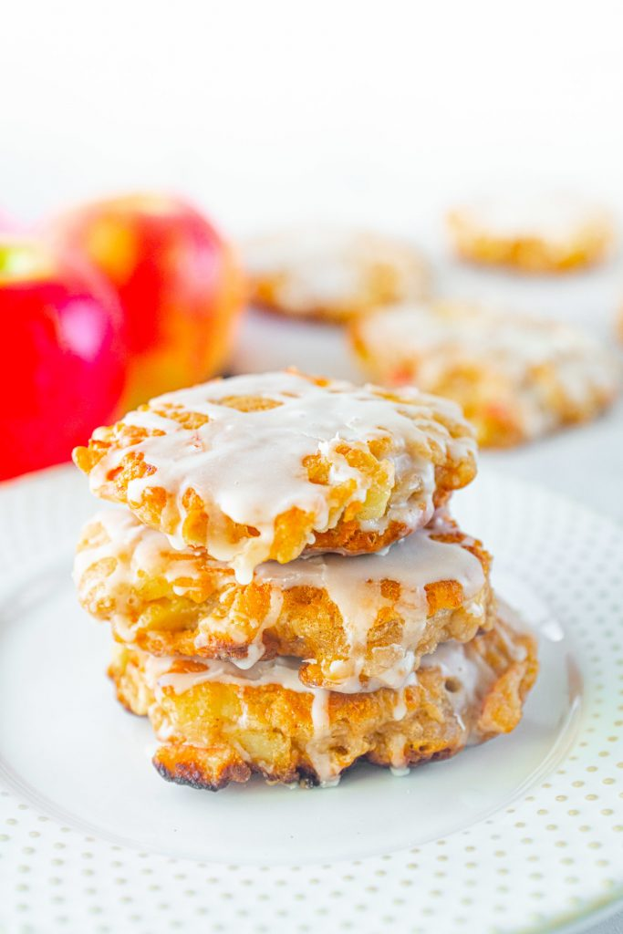 vegan apple fritters stacked on top of each other and glazed