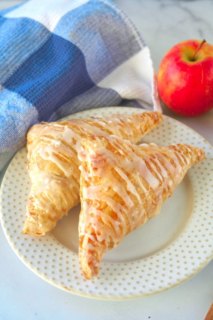two vegan apple turnovers on a plate with an apple in the background