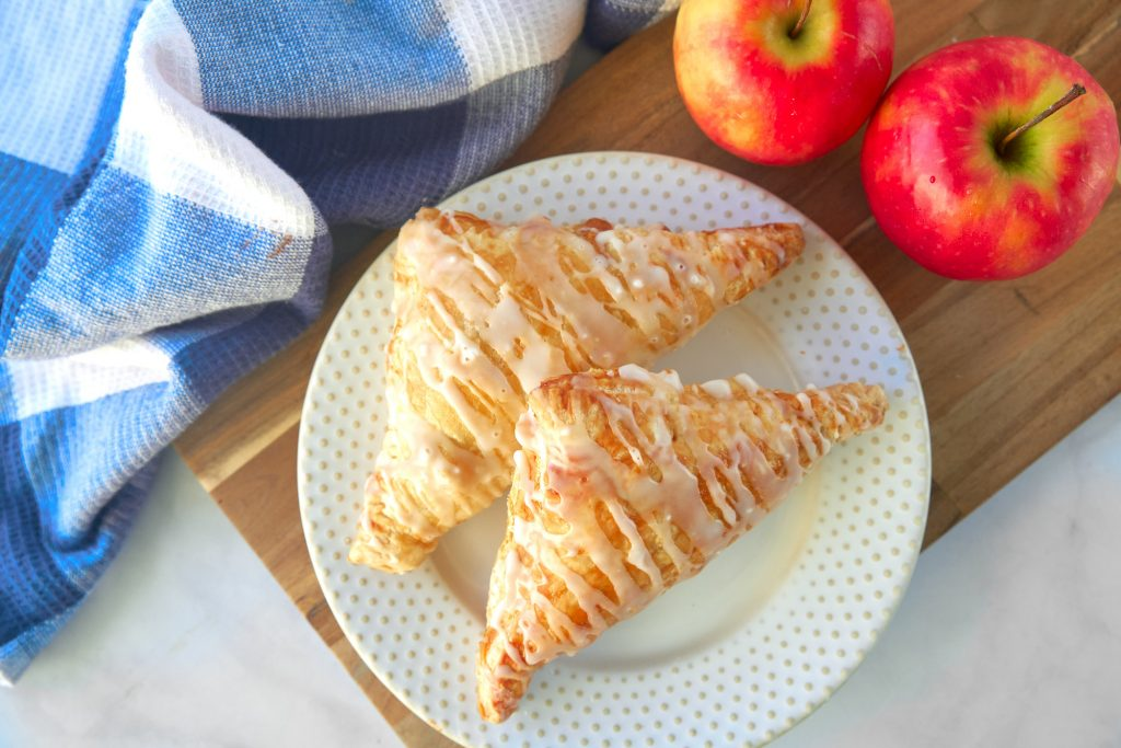 two vegan apple turnovers on plate with apples and dish towel