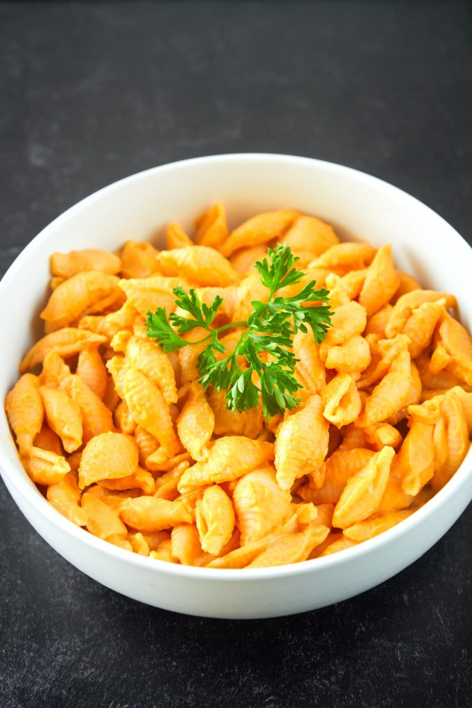 creamy vegan butternut squash mac and cheese with parsley leaves
