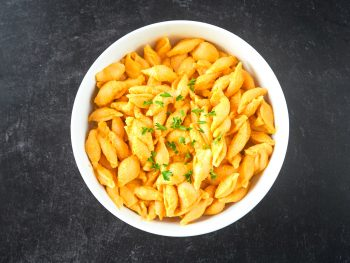photo of large bowl of vegan butternut squash mac and cheese on black counter