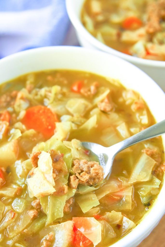 close up photo of vegan cabbage soup with spoon