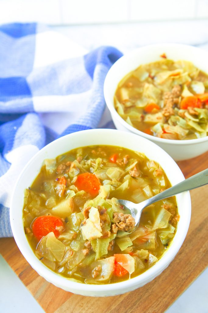 two bowls of vegan cabbage soup on cutting board