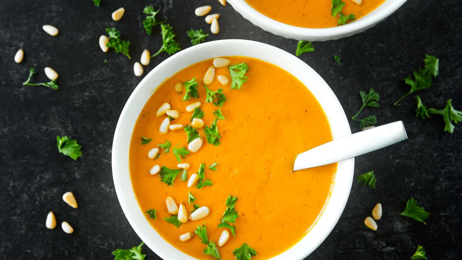 vegan carrot ginger soup portioned into two bowls on black background