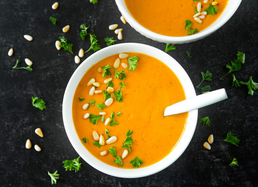 two bowls of vegan carrot soup on black background