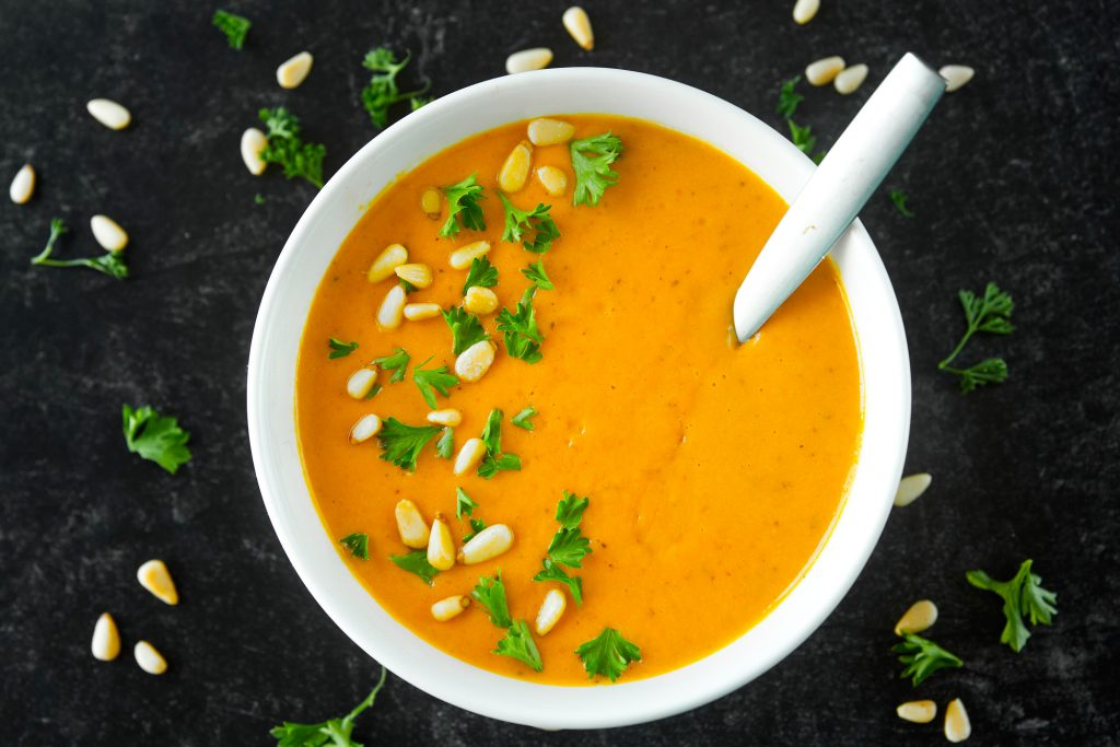 single bowl of vegan carrot ginger soup with soup spoon