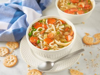 vegan chicken noodle soup with spoon and crushed crackers
