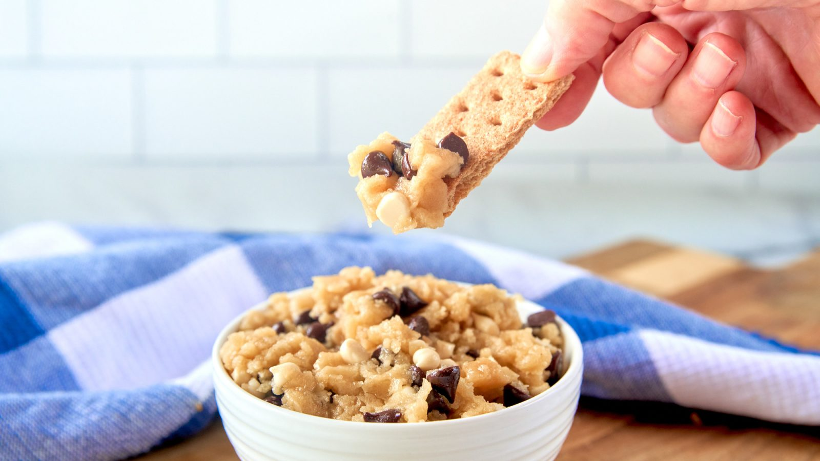 vegan cookie dough getting eaten by dipping a graham cracker into a bowl