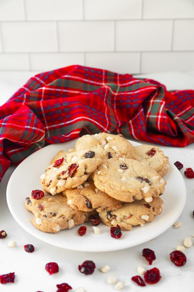 plate with vegan cranberry cookies with cranberries and white chocolate on counter