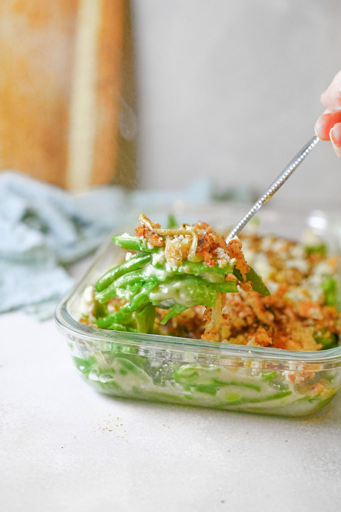 vegan green bean casserole being scooped out onto dish