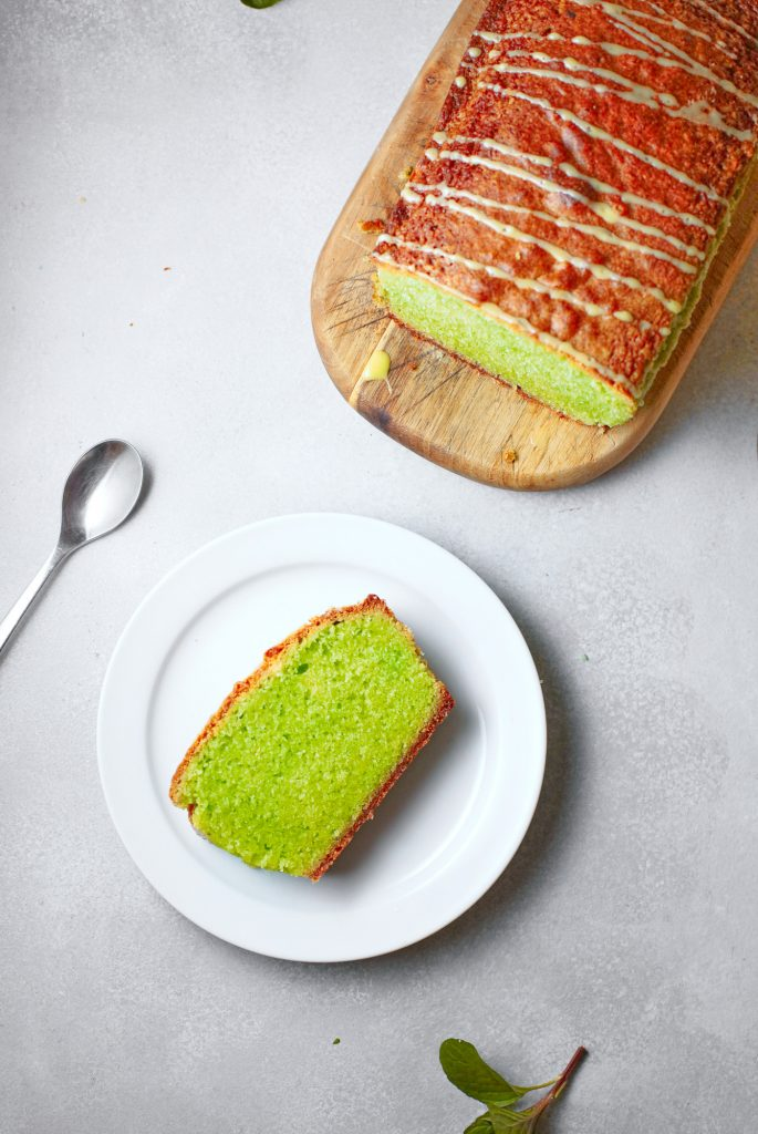 above a cut slice of vegan matcha cake with the loaf in the background
