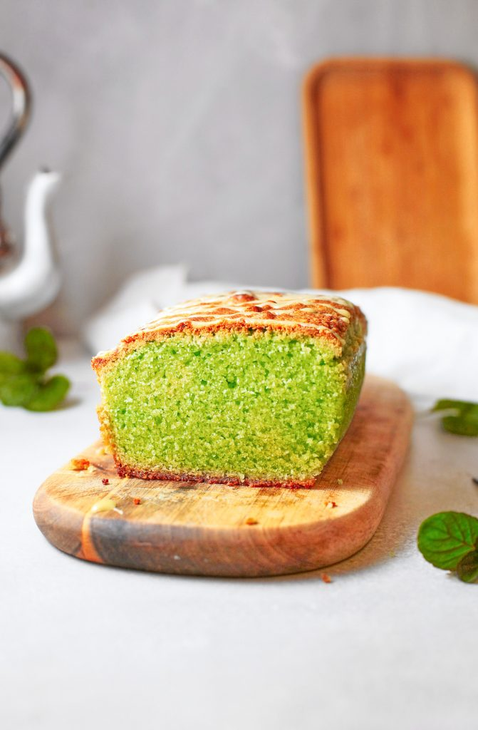 side view of a loaf of vegan matcha pound cake with mint