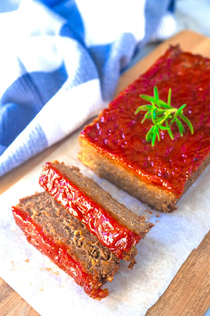 vegan meatloaf on serving tray with rosemary