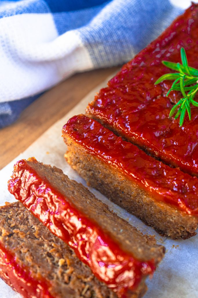 vegan meatloaf cut into slices with rosemary garnish