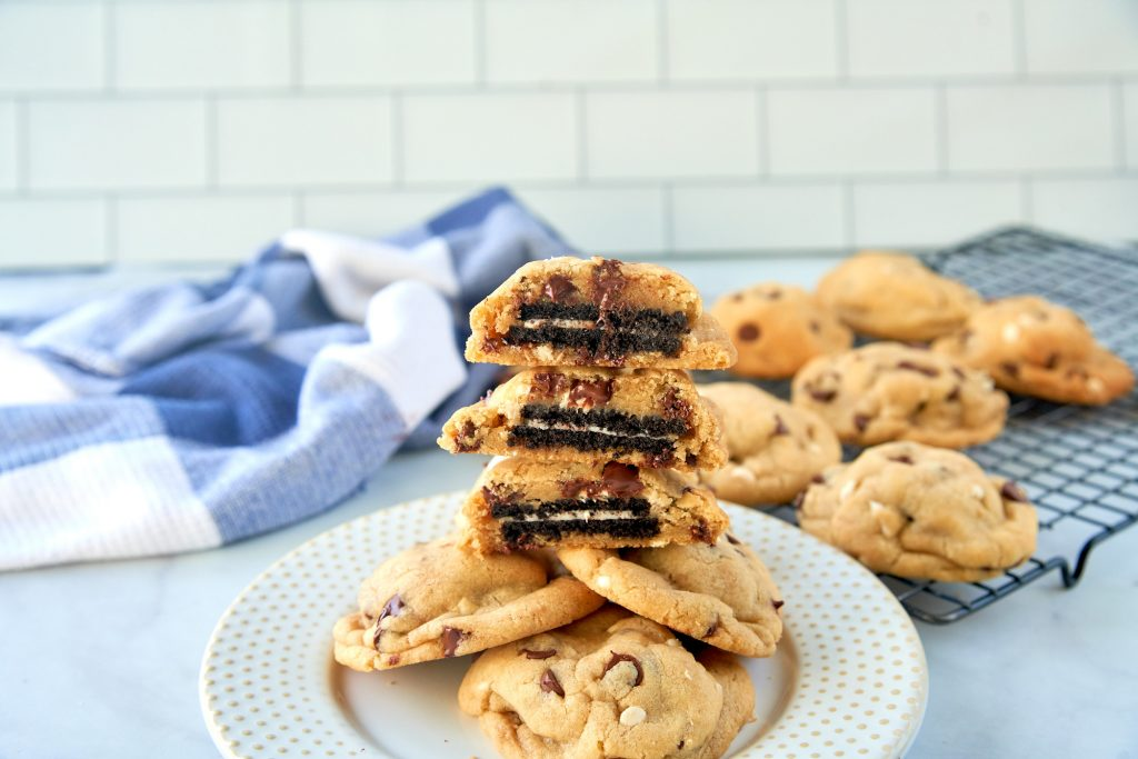 vegan oreo stuffed cookies stacked on plate and cut in half