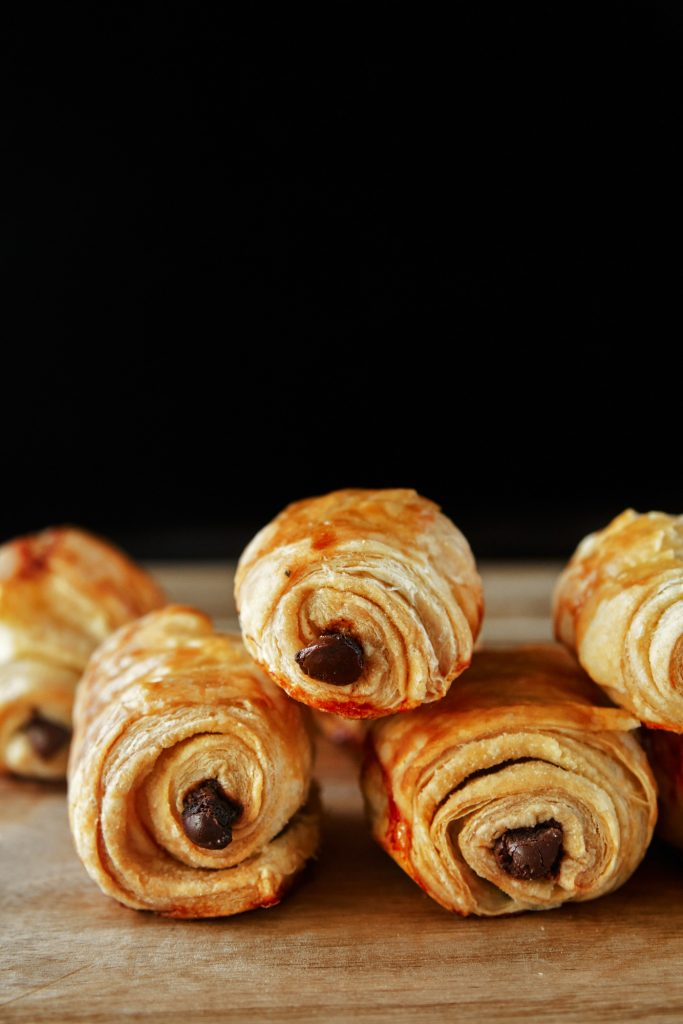vegan pain au chocolat rolls on a cutting board with black background