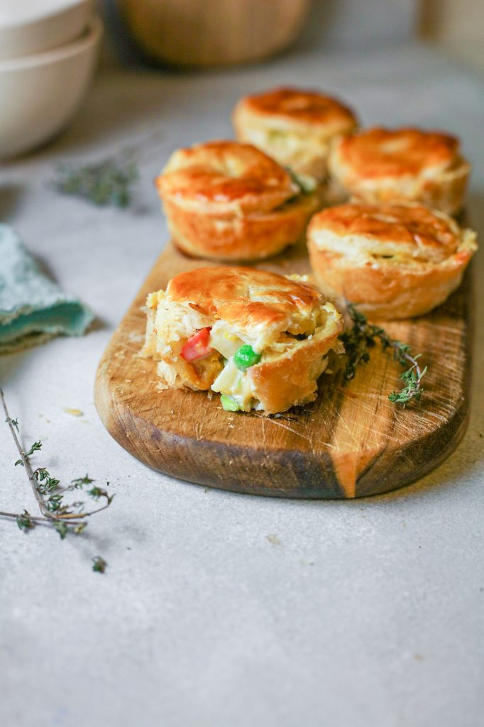 mini vegan pot pies on a serving tray with one cut open