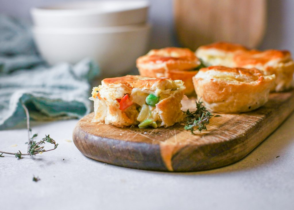 cut piece of vegan vegetable pot pie with filling spilling out
