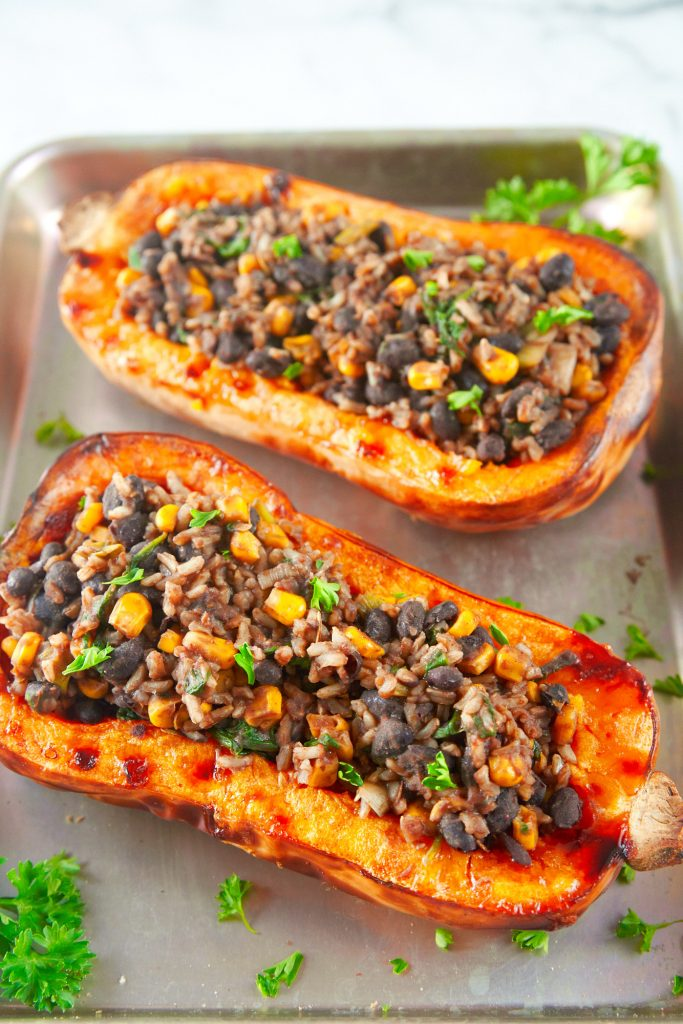 two vegan stuffed butternut squashes on a silver baking dish