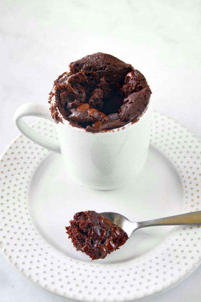 spoon with a scoop of vegan chocolate mug cake on a white plate