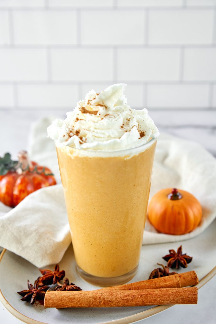 vegan pumpkin spice frappuccino in a tall glass with whipped cream and cinnamon
