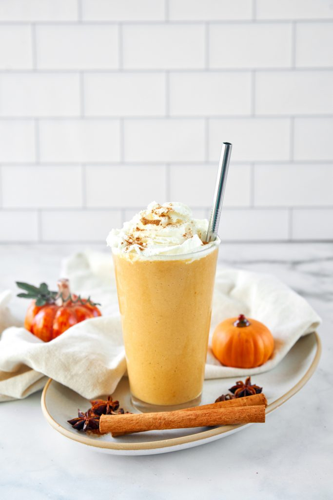 far away image of vegan pumpkin spice frappuccino with a metal straw