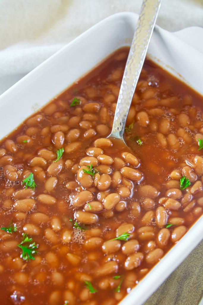 spoon in a dish of vegan baked beans