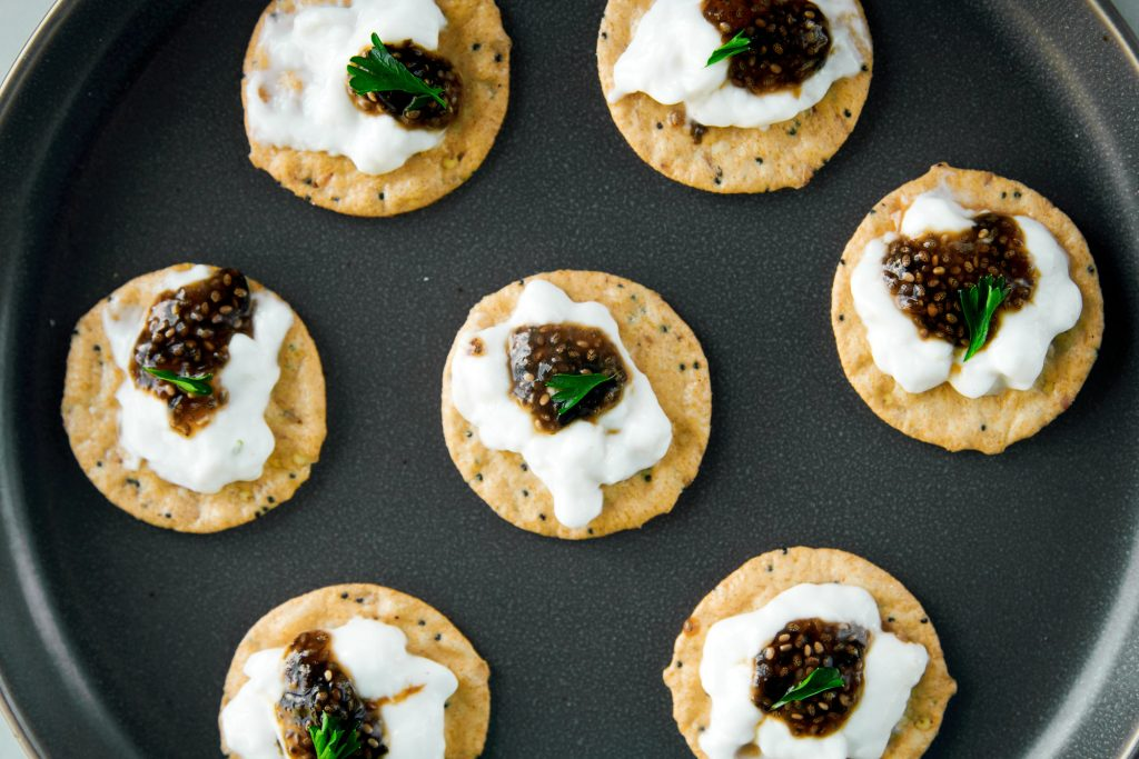 multiple crackers with sour cream and vegan caviar and herbs on them