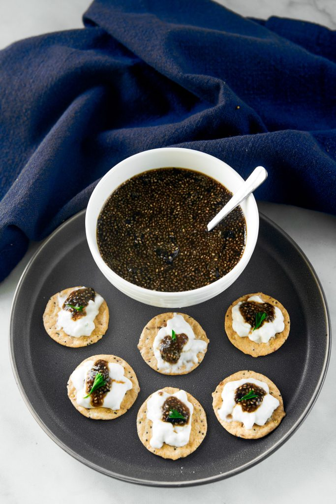 vegan caviar in a bowl with crackers all around it