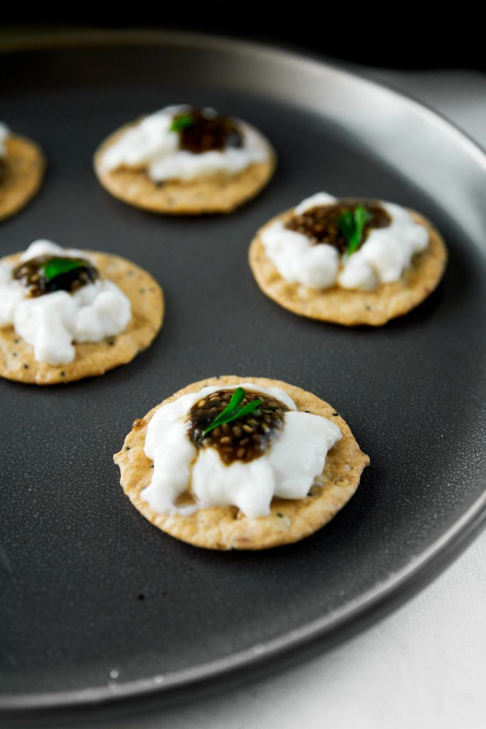 little crackers topped with sour cream and vegan caviar
