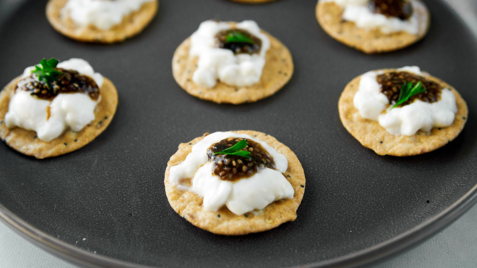 crackers topped with vegan caviar on a plate