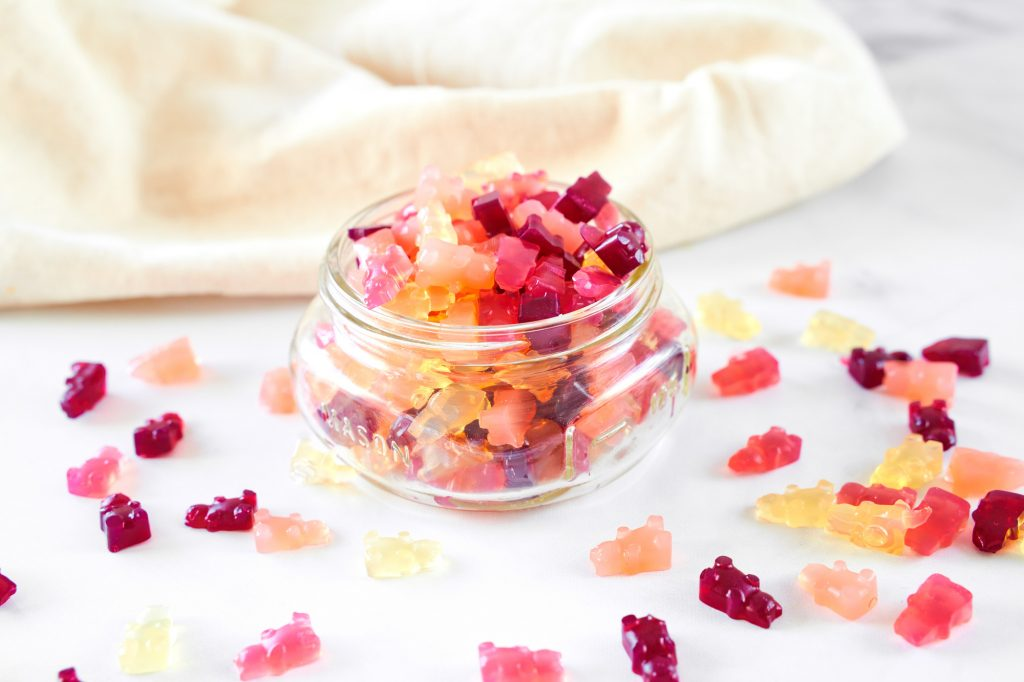 vegan gummy bears in a container spilling over the side and onto the counter