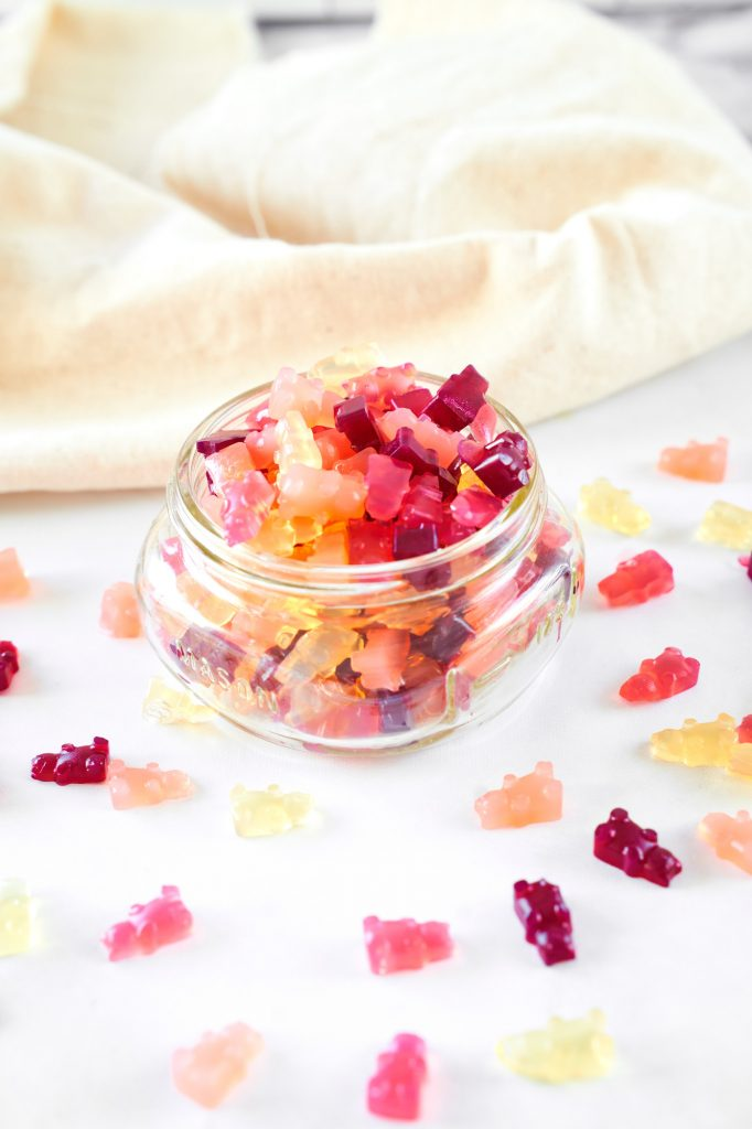 full vegan gummy bears recipe spilling out of a jar with some on the counter top