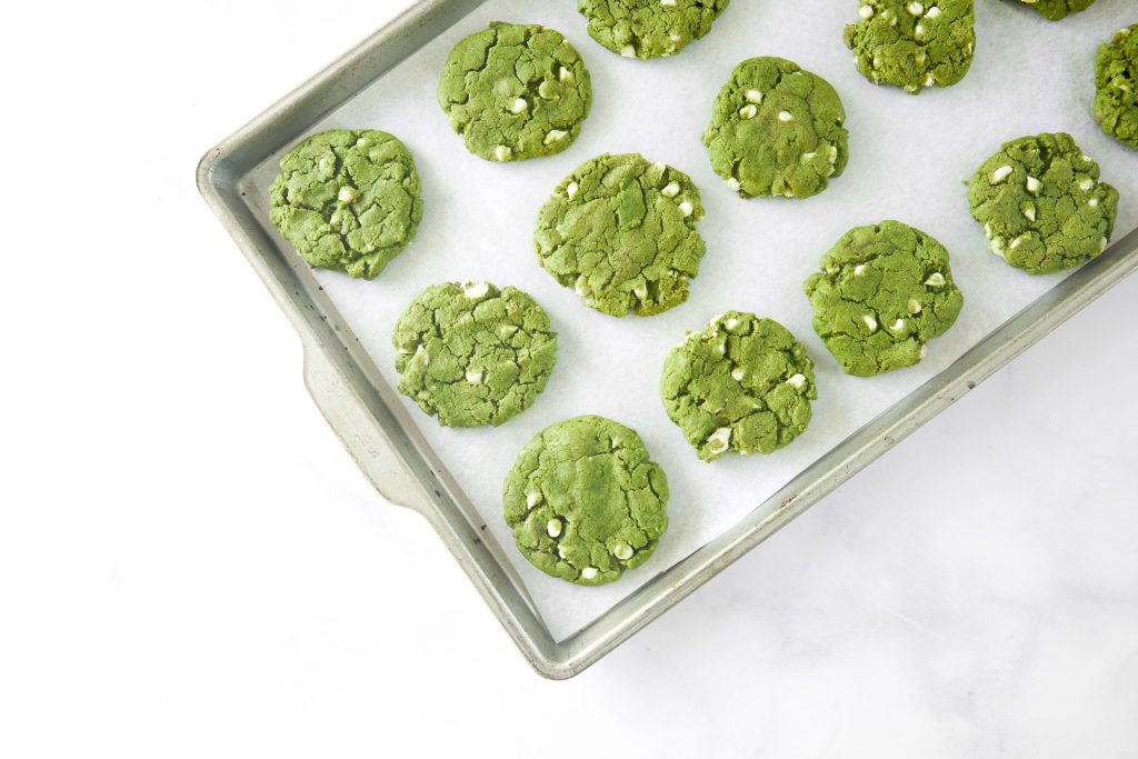 baking sheet with green tea cookies on it with white chocolate chips