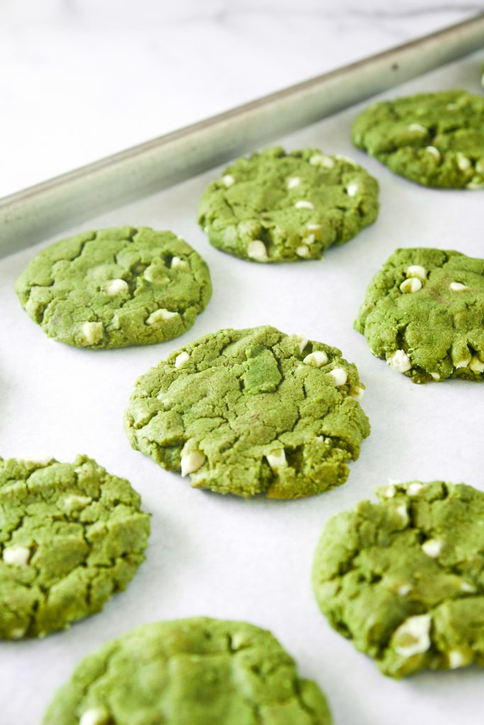 vegan matcha cookies with white chocolate chips on baking sheet