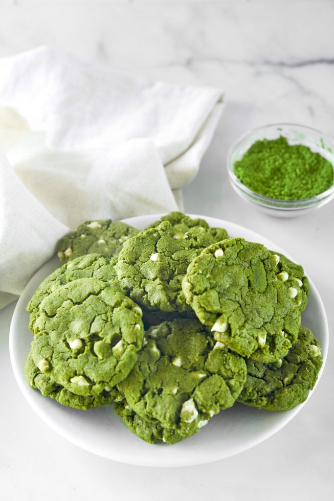 plate of vegan matcha cookies with matcha powder in the background