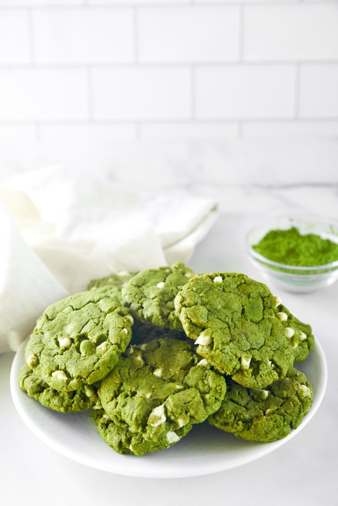 pile of vegan matcha cookies on serving plate with matcha in the background
