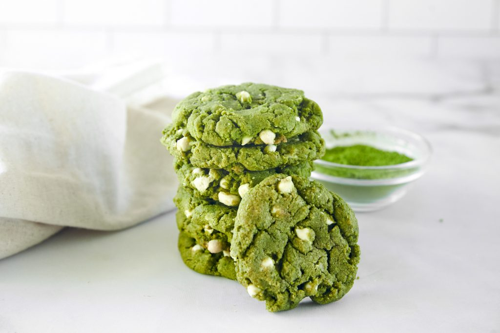vegan green tea cookies stacked with matcha powder in the background